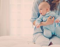 Happy middle aged mother with her child in a bed. Beautiful middle aged mother with her child in a bed stock images
