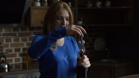 Pretty woman opening a wine bottle with corkscrew. Beautiful middle aged redhead woman opening a wine bottle with corkscrew in domestic kitchen. Steadicam stock video footage