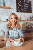 Beautiful middle aged waitress holding cup of coffee and smiling. At camera royalty free stock photography