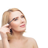 Beautiful middle aged woman applying eyebrow gel Royalty Free Stock Photo