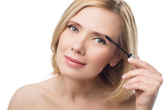 Beautiful middle aged woman applying eyebrow gel. Beautiful middle aged woman with smooth skin and short blond hair applying fix gel to eyebrows. Beauty shot Royalty Free Stock Photography