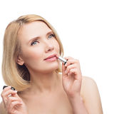 Beautiful middle aged woman applying lipstick Royalty Free Stock Images