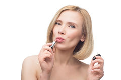 Beautiful middle aged woman applying lipstick. Beautiful middle aged woman with smooth skin and short blond hair applying lipstick. Beauty shot.  over white Royalty Free Stock Photography