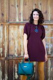 Beautiful middle-aged woman in a burgundy dress and green handbag. Near aged doors stock photo