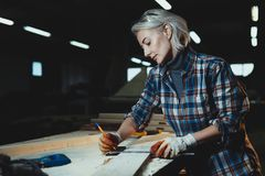 Beautiful middle aged woman carpenter designer works with ruler, make notches on the tree in workshop. Image of modern femininity royalty free stock photos