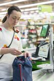Beautiful middle-aged woman at the checkout in the supermarket.  Royalty Free Stock Images