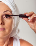 Beautiful middle aged woman. Cropped image of beautiful middle aged woman with a towel on her head using a mascara, on a gray background Stock Photos