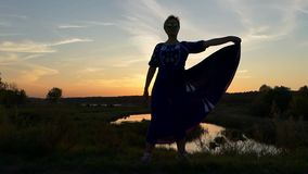 Middle-aged woman in a folk dress stands at sunset stock footage