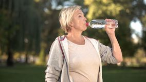 Beautiful middle aged woman drinking water after finishing her morning workout royalty free stock images
