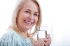 Beautiful middle aged woman drinking water in the morning Stock Image