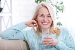 Beautiful middle aged woman drinking water in the morning. Woman`s face close up stock photography