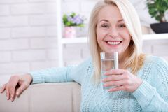 Beautiful middle aged woman drinking water in the morning Stock Images