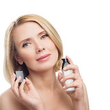 Beautiful middle aged woman with face serum. Beautiful middle aged woman with smooth skin and short blond hair applying face serum. Beauty shot. Isolated over Royalty Free Stock Image