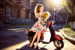 beautiful middle-aged woman with flowers and curly hair sits on a scooter in a dress Stock Photo