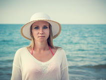 Beautiful middle-aged woman in hat on the beach. Royalty Free Stock Images