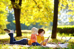 Beautiful middle aged woman and her adorable little grandson having a picnic in sunny park Royalty Free Stock Photo