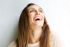 Beautiful middle aged woman laughing against white background Royalty Free Stock Images