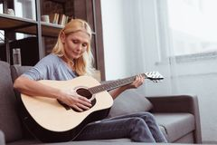 Beautiful middle aged woman playing guitar while sitting on sofa. At home stock image