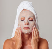 Beautiful middle aged woman. Portrait of beautiful middle aged woman with a towel on her head and a mask on her face, standing with closed eyes on a gray Stock Photography
