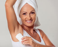 Beautiful middle aged woman. Portrait of beautiful middle aged woman with a towel on her head using a deodorant, looking at camera and smiling, on a gray Royalty Free Stock Photos