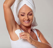 Beautiful middle aged woman. Portrait of beautiful middle aged woman with a towel on her head using a deodorant and smiling, on a gray background Stock Photos