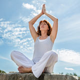 Beautiful middle aged woman praying in yoga position Stock Image