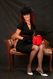 A beautiful middle-aged woman with a red gift Stock Image