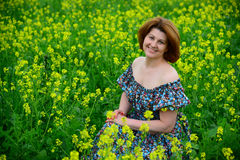 Beautiful middle-aged woman sitting in flowering meadow. Beautiful middle-aged woman sitting in a flowering meadow Royalty Free Stock Photography