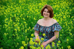 Beautiful middle-aged woman sitting in flowering meadow. Beautiful middle-aged woman sitting in a flowering meadow Stock Photo
