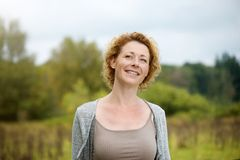 Beautiful middle aged woman smiling outdoors. Close up portrait of a beautiful middle aged woman smiling outdoors Stock Photo