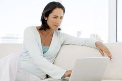Beautiful middle aged woman using laptop at home royalty free stock images