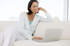 Beautiful middle aged woman using laptop at home royalty free stock photography