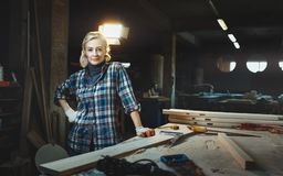 Beautiful middle aged woman worker posing against background of a woodworking workshop. Concept of motivated women, gender royalty free stock photography