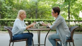 Beautiful middle-aged women chatting holding coffee cups in outdoor cafe
