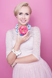 Beautiful middle aged women hold colorful donut. Soft colors Stock Photography