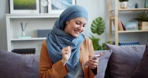 Beautiful Middle Eastern woman in hijab using smartphone at home smiling. Beautiful Middle Eastern woman in hijab is using smartphone at home smiling enjoying stock footage