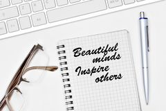 Beautiful minds inspire others. Text on notebook on white background. Beautiful minds inspire others. Text on notebook on a white background close-up Stock Photography