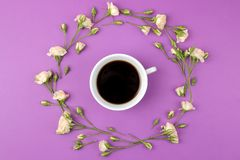 Beautiful mini roses and a cup of coffee on a bright lilac background. holidays. Valentine`s Day. women`s Day. top view stock photo