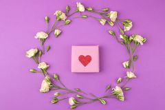 Beautiful mini roses and gift box on a bright lilac background. holidays. Valentine`s Day. women`s Day. top view stock images