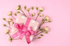 Beautiful mini roses with a pink gift box on a bright pink background. holidays. Valentine`s Day. women`s Day. top view royalty free stock images
