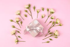 Beautiful mini roses with a pink gift box on a bright pink background. holidays. Valentine`s Day. women`s Day. top view royalty free stock photography