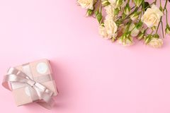 Beautiful mini roses with a pink gift box on a bright pink background. holidays. Valentine`s Day. women`s Day. top view. space f. Or text stock image