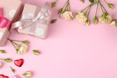 Beautiful mini roses with a pink gift box on a bright pink background. holidays. Valentine`s Day. women`s Day. top view. space f. Or text royalty free stock photography