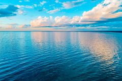 Beautiful minimalism - clouds over calm sea. Beautiful minimalism - clouds over calm sea water at sunrise royalty free stock photo