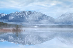 Beautiful misty morning on lake in Alps Stock Images