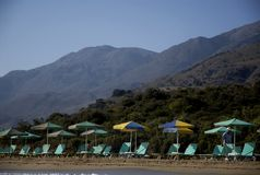 Cheerful beach umbrellas and watercolor mountains. Beautiful misty mountains of Crete and funny beach umbrellas and none of the tourists Stock Image