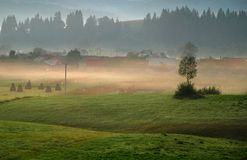 Beautiful misty sunrise over the village royalty free stock image