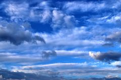 Beautiful mixed cloud formations with white and grey cumulus clouds in the sunlight on a blue sky. Seen in germany royalty free stock photo