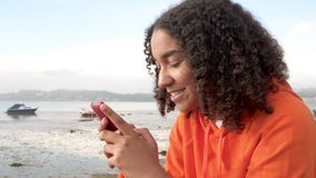 Beautiful mixed race African American girl teenager using her smart cell phone for social media or texting stock video
