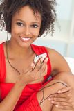 African American Girl Listening to MP3 Player Headphones. A beautiful mixed race African American girl or young woman wearing a red dress listening to music on Royalty Free Stock Photography